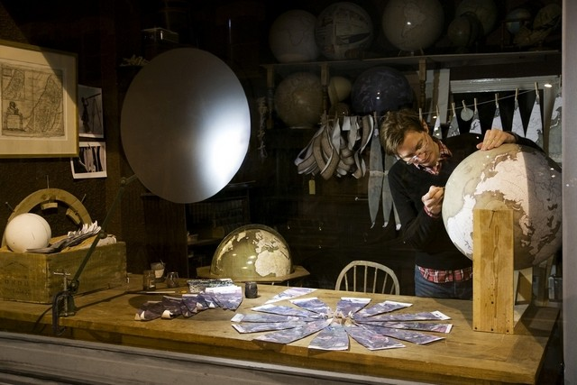Peter Bellerby working on a handcrafted globe in his London studio. Gores for a celestial globe are laid out on in front of him. Photo by Tanja Schimpl