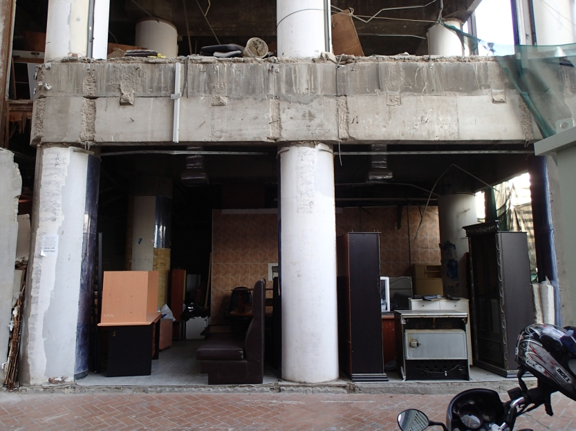 Salvage men sell what remains of the building's contents from a makeshift junk shop on the ground floor