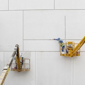 Workers repair minor imperfections to the ultra-high performance fibre reinforced concrete panels that form the cladding of the Louvre Abu Dhabi. Antonie Robertson / The National